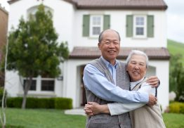 Picture of a Happy Elderly Couple Smiling From the Lawn of Their House